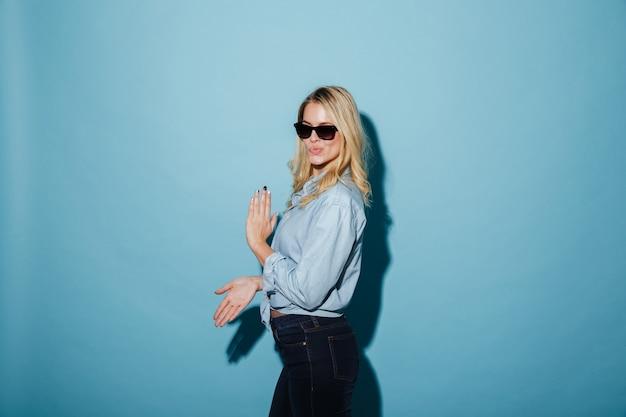 Vue latérale d'une femme blonde heureuse en chemise et lunettes de soleil