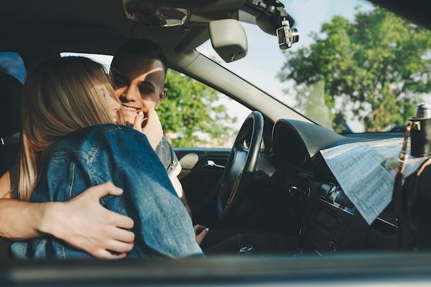 Vue latérale d'une femme blonde souriante embrassant et tenant la main au visage de joyeux jeune homme assis au volant de voiture avec carte se trouvant sur le tableau de bord