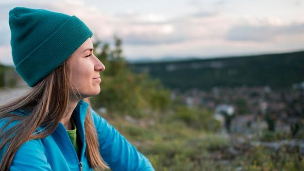 Vue latérale femme avec bonnet appréciant la vue
