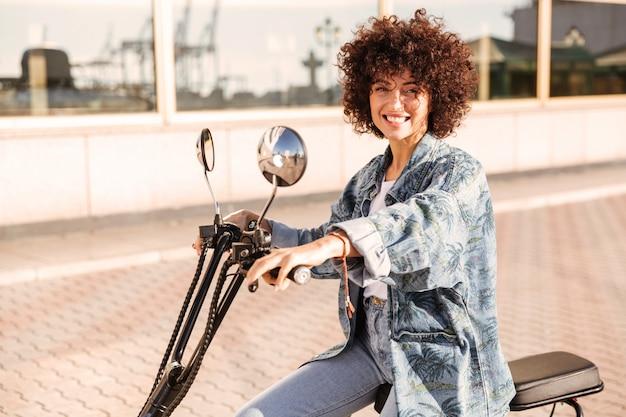 Vue latérale d'une femme bouclée heureuse assise sur une moto moderne