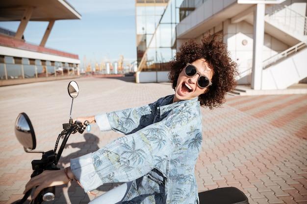 Vue latérale d'une femme bouclée heureuse insouciante à lunettes posant sur une moto moderne à l'extérieur
