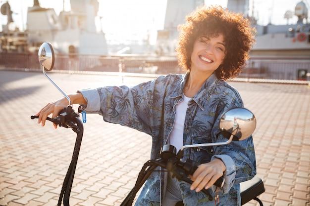 Vue latérale d'une femme bouclée souriante assise sur une moto moderne à l'extérieur