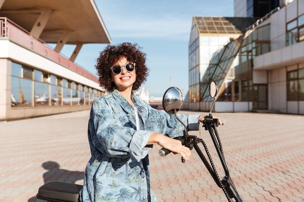 Vue latérale d'une femme bouclée souriante à lunettes posant sur une moto moderne à l'extérieur