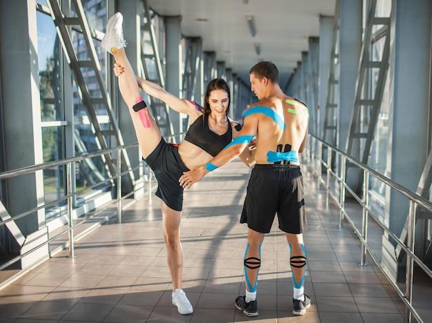 Vue latérale d'une femme brune flexible musclée pratiquant la division, tenant la jambe