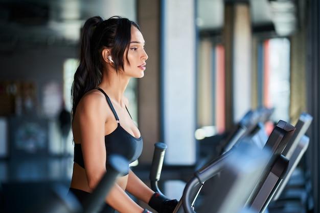 Vue latérale d'une femme brune en vêtements de sport noirs et écouteurs sans fil faisant un entraînement cardio dur sur orbitrek.