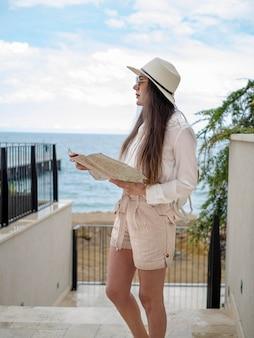 Vue latérale femme avec carte au bord de mer