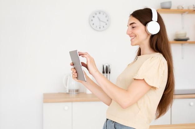 Vue latérale femme avec un casque en choisissant une chanson de son ordinateur portable
