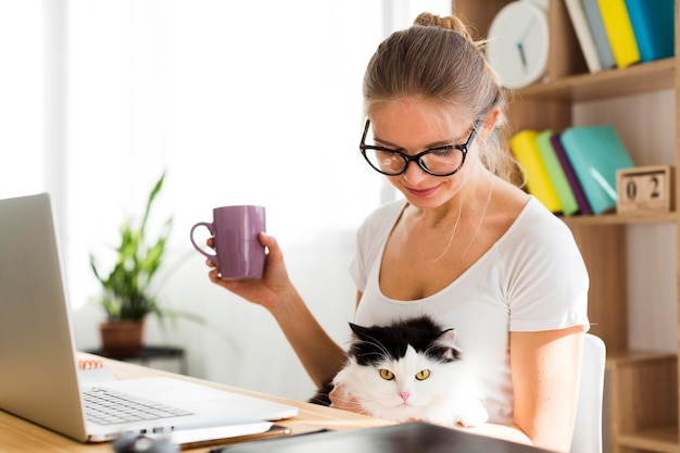 Vue latérale d'une femme avec un chat au bureau travaillant à domicile