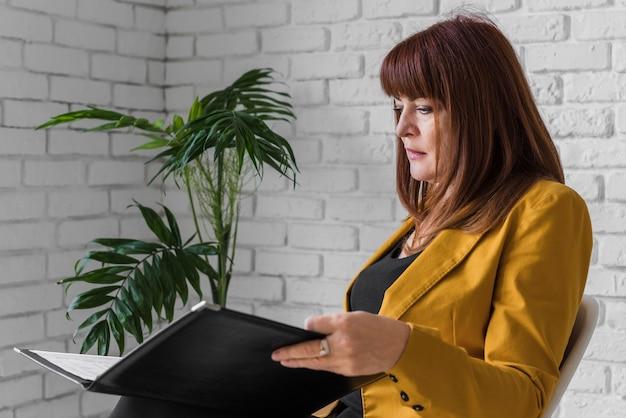 Vue latérale femme consultant presse-papiers