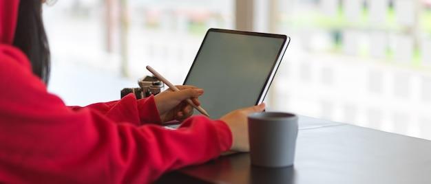 Vue latérale de la femme dans les mains de chandail rouge travaillant avec maquette de tablette numérique au café