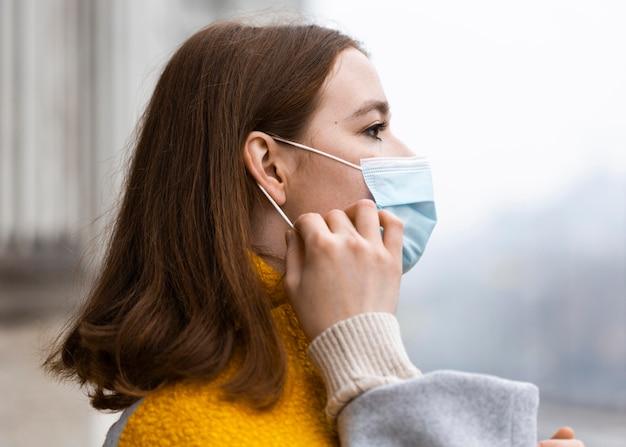 Vue latérale de la femme dans la ville ajustant son masque médical