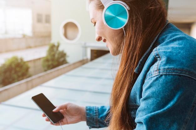 Vue latérale d'une femme écoutant de la musique sur un casque tout en utilisant un smartphone