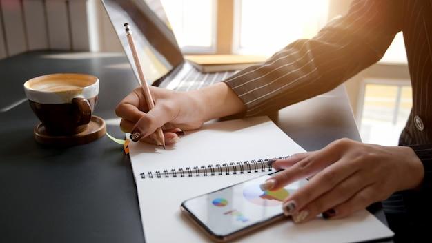 Vue latérale d'une femme écrivant sur un ordinateur portable tout en regardant le tableau des affaires sur smartphone
