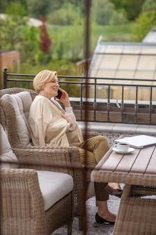 Vue latérale d'une femme élégante blonde satisfaite assise en tailleur dans le fauteuil à une table en bois sur la véranda
