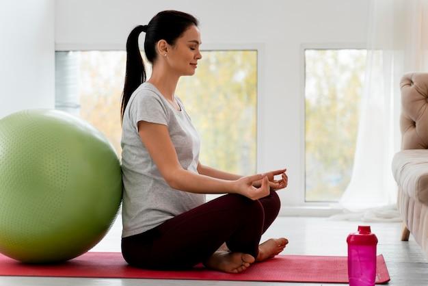 Vue latérale d'une femme enceinte méditant avec espace copie