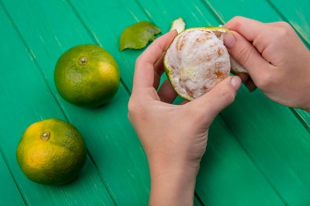 Vue latérale femme épluche la peau de mandarine sur le mur vert