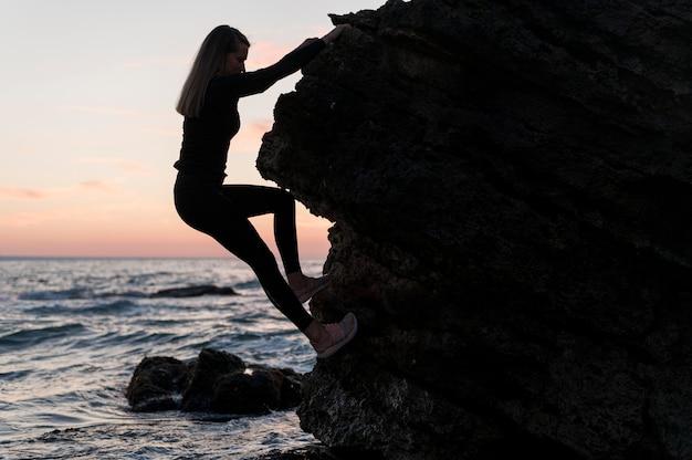 Vue latérale femme escalade un rocher à côté de l'océan