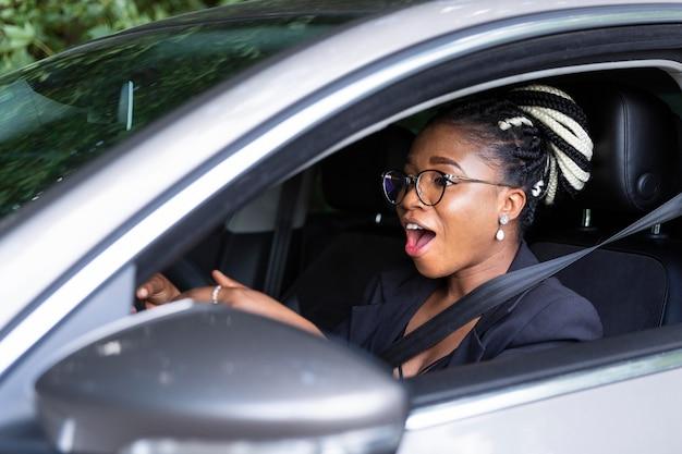 Vue latérale de la femme excitée de conduire sa voiture personnelle