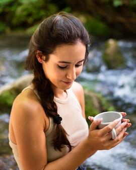 Vue latérale d'une femme explorant la nature et buvant du café