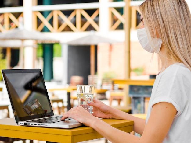 Vue latérale d'une femme à l'extérieur avec un masque facial travaillant sur un ordinateur portable