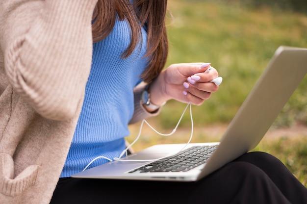 Vue latérale d'une femme à l'extérieur avec un ordinateur portable et des écouteurs