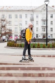 Vue latérale d'une femme faisant du patin à roues alignées dans la ville