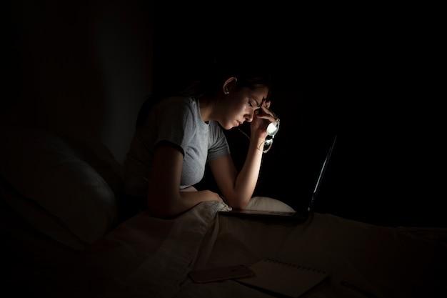Vue latérale d'une femme fatiguée travaillant tard à la maison
