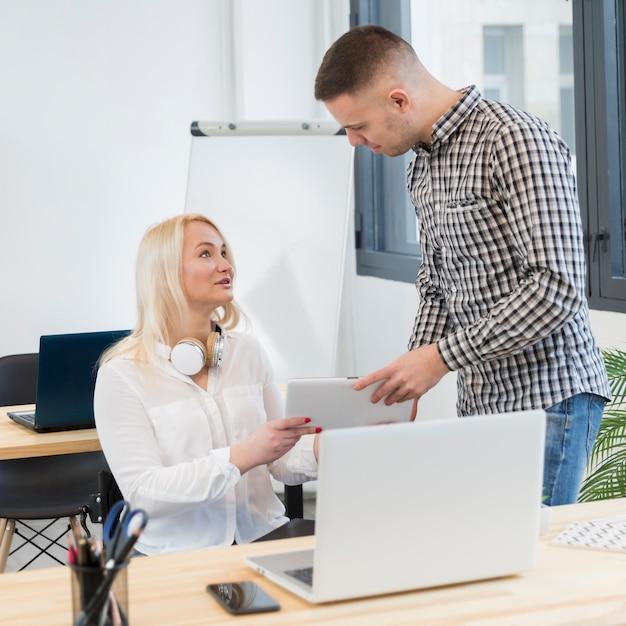 Vue latérale d'une femme en fauteuil roulant et collègue tenant une tablette