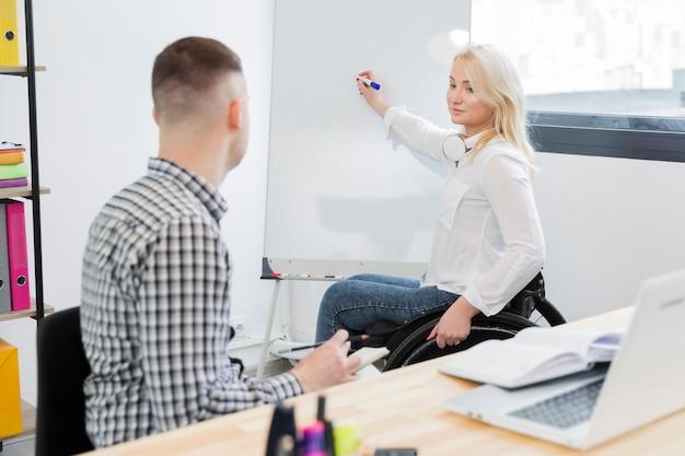Vue latérale d'une femme en fauteuil roulant donnant une présentation à un collègue