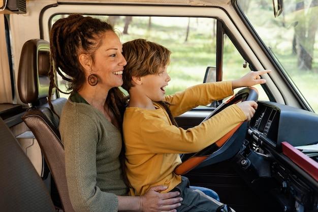 Vue latérale femme avec fils sur ses genoux au volant