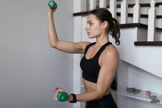 Vue latérale d'une femme fléchissant les bras pendant l'exercice avec des poids