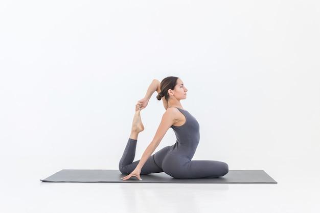 Vue latérale d'une femme flexible yogi pratiquant des exercices de yoga sur tapis sur fond blanc en studio