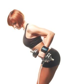 Vue latérale d'une femme en forme rousse faisant une extension de triceps haltère à deux bras plié. prise de vue en studio, fond blanc, isolé