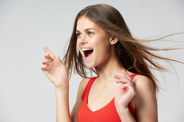 Vue latérale d'une femme heureuse avec la bouche ouverte gesticulant avec les mains sur un fond clair et en riant
