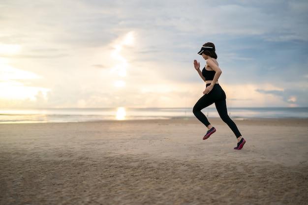 Vue latérale d'une femme jogging sur la plage le matin.