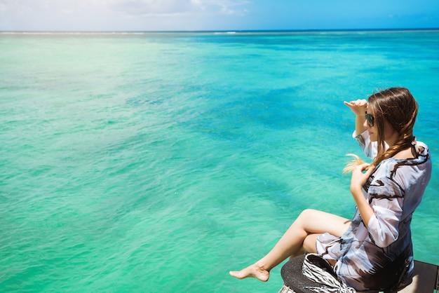 Vue latérale d'une femme joyeuse assise sur la jetée en admirant l'océan fantastique
