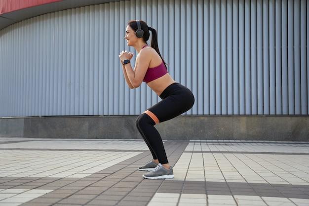 Vue latérale d'une femme en leggings noirs faisant des squats et utilisant des élastiques de fitness. notion de sport. espace de copie