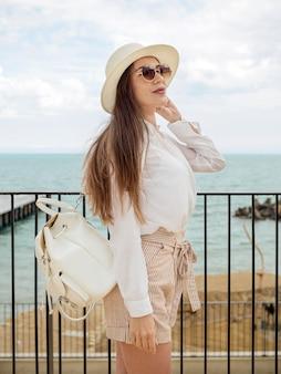 Vue latérale femme avec des lunettes de soleil