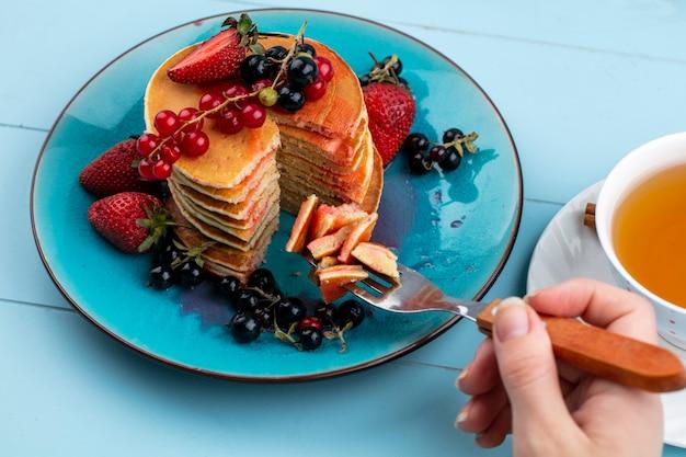 Vue latérale d'une femme mange des crêpes aux fraises rouges et cassis et une tasse de thé sur une surface bleue