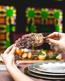 Vue latérale une femme mange entrecôte kebab viande rib avec graines de sésame et coquelicots