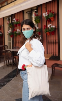 Vue latérale d'une femme avec un masque facial et des sacs d'épicerie à l'extérieur