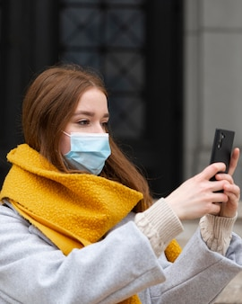 Vue latérale d'une femme avec un masque médical à prendre des photos avec un smartphone