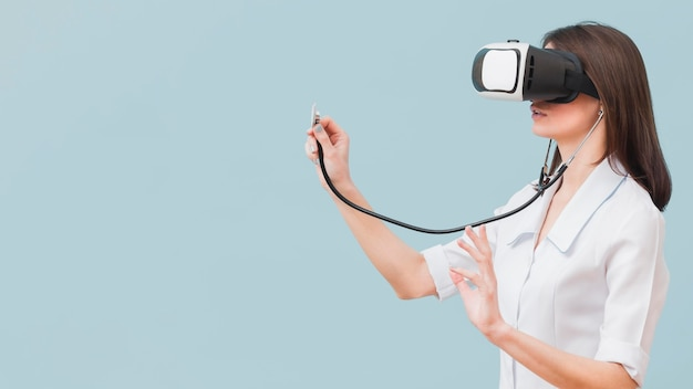 Vue latérale d'une femme médecin à l'aide d'un stéthoscope et d'un casque de réalité virtuelle