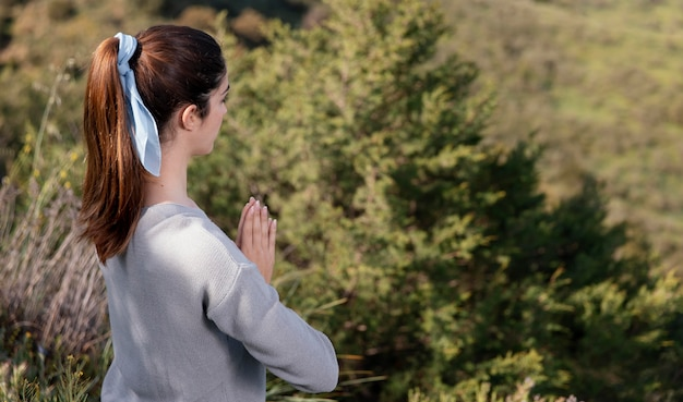 Vue latérale femme méditant dans la nature