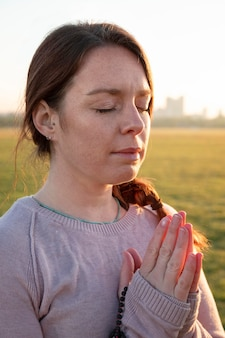 Vue latérale d'une femme méditant à l'extérieur