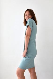 Vue latérale d'une femme mince et positive portant une robe bleue dans un style décontracté debout sur fond blanc en studio et regardant loin