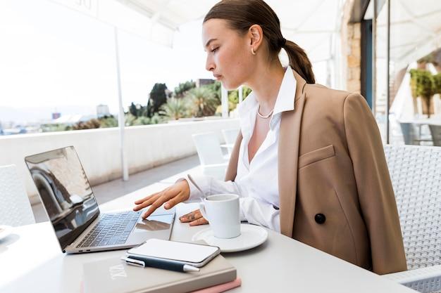 Vue latérale femme occupée travaillant à l'extérieur