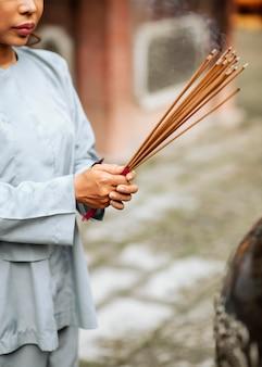 Vue latérale de la femme avec un paquet d'encens brûlant au temple