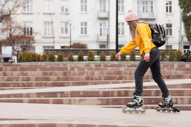 Vue latérale d'une femme en patins à roues alignées avec espace copie