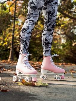 Vue latérale d'une femme avec des patins à roulettes et des jambières